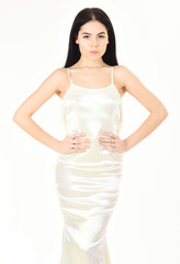 Slim and fit concept. Fashion model with slim figure as result of dieting and fitness. Lady on calm face wears expensive fashionable evening dress. Woman in elegant white dress, white background.