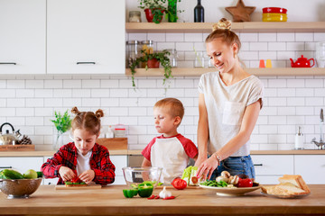Image of young mother with daughter and son cutting vegetables at table