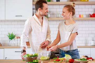 Picture of loving couple cooking vegetables in kitchen