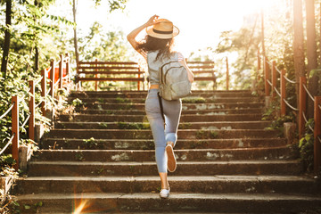 Photo from back of young woman 18-20 wearing summer clothes and straw hat, running up stairs in green park on sunny day Fototapete