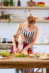 Picture of young mother with her daughter cooking food in kitchen