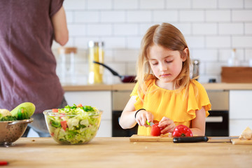 Image of man with daughter cooking vegetables