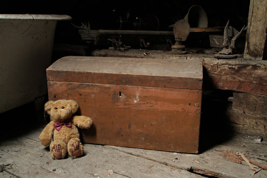 Childs teddy bear and an old chest in the dusty attic space of an old house