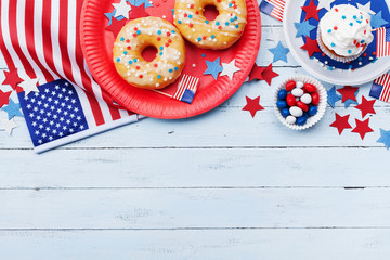 Independence Day background on 4th of July with american flag, stars and food on wooden table top view.