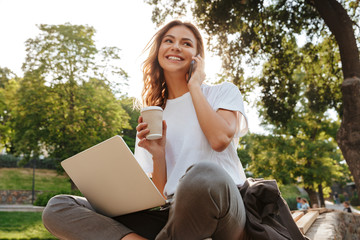 Image of smiling modern woman sitting on bench in green park on summer day, and talking on smartphone while using silver laptop and drinking takeaway coffee - fototapety na wymiar
