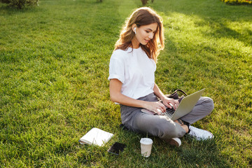 Photo of european woman 20s sitting on green grass in park with legs crossed during summer day, while using laptop and bluetooth earpod