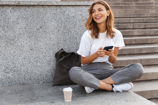 Image of beautiful stylish woman sitting on street stairs with legs crossed on summer day, and holding mobile phone