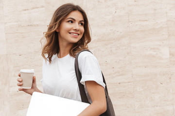 Portrait of young european woman walking against beige wall outdoor with silver laptop, and takeaway coffee in hands
