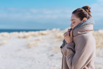 Frau steht im winter am strand und kuschelt sich in ihren mantel