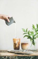Iced coffee in tall glasses with milk poured over from pitcher by hand, white wall and green plant branches in vase at background, copy space. Summer refreshing beverage