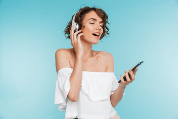 Portrait of a delighted young woman listening to music