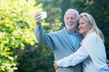 Happy senior couple taking a selfie, outdoors