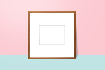 empty white space in wooden blank frame leaning against with pink wall and blue floor. simple blank photo frame for presentation or decorate background