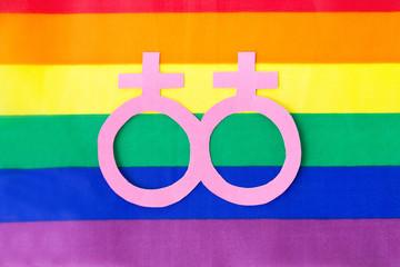 gay pride, homosexual and lgbt concept - venus or female gender symbol on rainbow flag background
