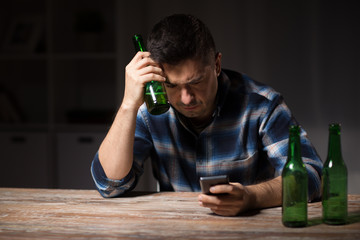alcoholism, alcohol addiction and people concept - drunk man with smartphone and bottle of beer at night
