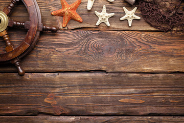 Wooden steering wheel, starfish and fishing net on wooden wall background
