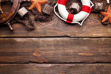 Ship's steering wheel, lifebuoy, flashing net and seashells on wooden board