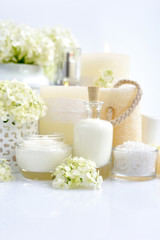 Spa composition with candles, cream, salt and flowers of hydrangea on a white background