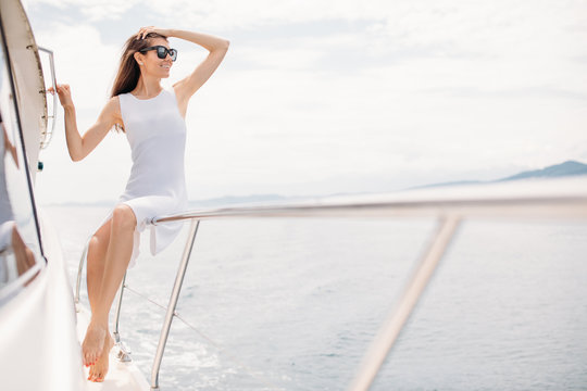 Dreaming caucasian woman in white dress wearing sunglasses sitting on railings of a luxury boat. Outdoors, lifestyle