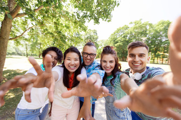 people, friendship and international concept - happy smiling young woman and group of happy friends taking selfie outdoors