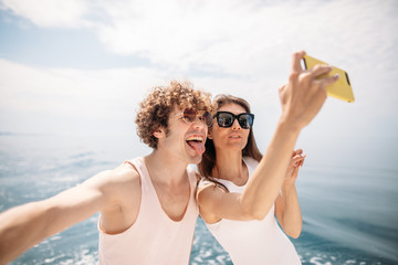 Vacation, sailing, tourism, travel and people concept - happy young couple with smartphone taking selfie on sail boat or yacht deck floating in sea over amazing sea background