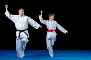 Male karate instructor training little children in dojo