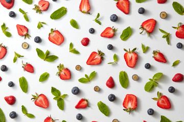 fruit pattern with half strawberries, blueberries and mint leaves on a white background, top view