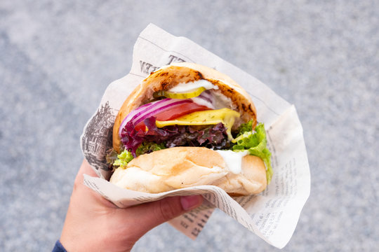 Hand of a young man holding an organic vegan burger with seitan patty in his hand during a street food festival