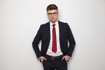 portrait of relaxed young businessman standing with hands in pockets