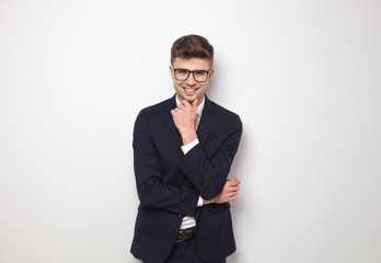 handsome businessman wearing navy suit and glasses standing and thinking
