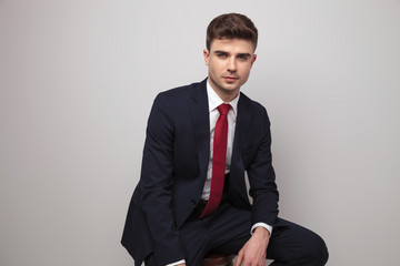 sexy young businessman in navy suit sits on wooden stool