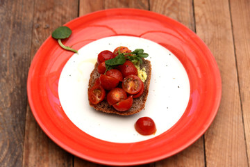 Fresh tomatoes on wholemeal toast, served on a red and white plate.