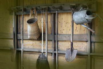 Old garden tools hanging up in a shed.