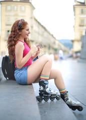 Girl sitting in the street, wearing roller skates