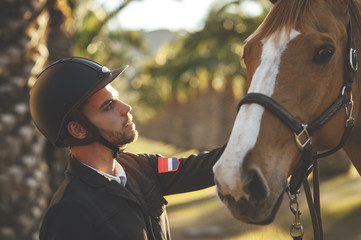 Portrait of young handsome horserider looking with affection to his brown horse in a palm trees avenue on summer day at sunset