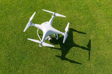 White drone camera in front of green grass from above