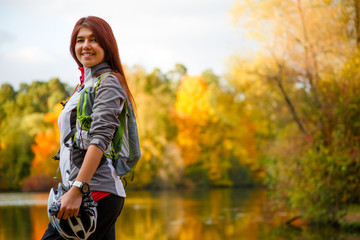 Image of smiling woman with backpack and bicycle helmet