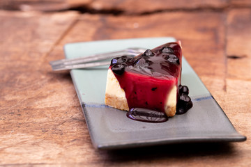 Tasty and delicious cheesecake dessert with berry fruit made on top served plate on wooden table.
