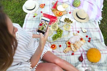 Young girl making food photo at picnic