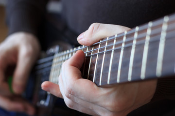 Man is playing guitar close up