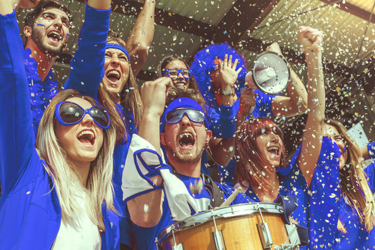 group of fans dressed in blue color watching a sports event