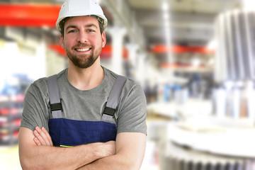 closeup Portrait of a friendly workmen in mechanical engineering //  freundlicher Monteur im Maschinenbau - im hintergrund Fabrikhalle zur Herstellung von Getrieben