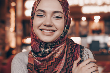 smiling Arab girl with a headscarf sitting in a beautiful restaurant, waiting for her food
