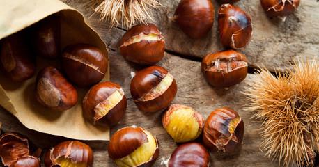 Roasted Sweet Chestnuts nuts on neutral wooden background closeup, macro, detail -  healthy seasonal snack.