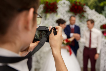 Photographer taking a photo of the happy marriage couple during the wedding ceremony. Selective focus.