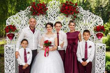 Happy bride and groom with family, looking at camera. After wedding ceremony near wedding arch. Marsala style. Outdoors.
