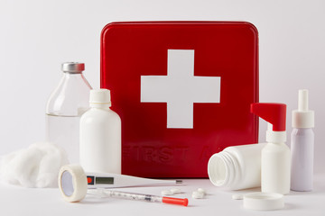 close-up shot of red first aid kit box with various medical bottles and supplies on white