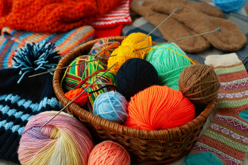 Balls of yarn for knitting in the basket. Lots of colorful yarn balls in a wicker basket. Knitting clothes as a kind of needlework.