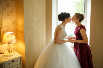 Side view of mother while kissing her daughter and holding her hands at her wedding day. At home.