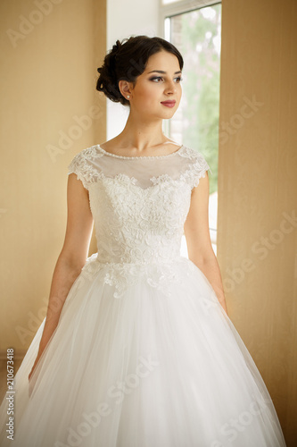 Portrait of gorgeous young bride in luxury wedding dress looking at ...